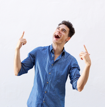 Retrato de un joven alegre que señala los dedos para copiar el espacio sobre fondo blanco Foto de archivo - 44122637