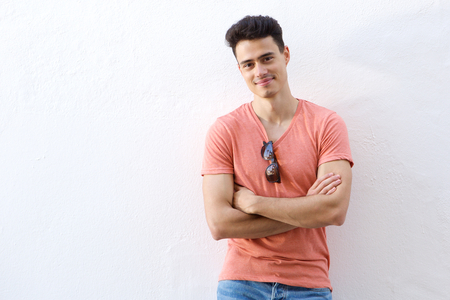 handsome young man: Portrait of a confident young man smiling with arms crossed against white background Stock Photo