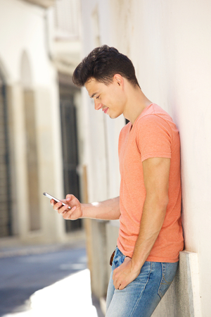young man portrait: Portrait of a handsome young man reading text on mobile phone