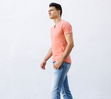 face side: Side portrait of a cool young guy walking against white background