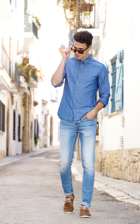 cool guy: Full body portrait of a cool young guy walking on street in town