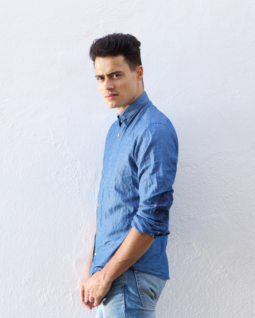 good looking model: Portrait of a handsome young man in denim blue shirt staring