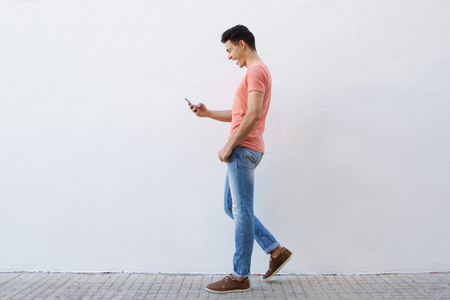 Full length side portrait of a cheerful young man walking on sidewalk and reading text message on mobile phone
