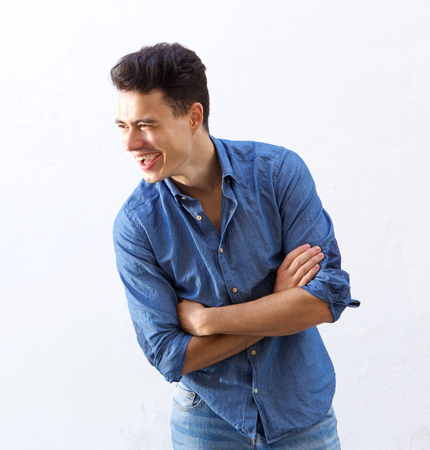 denim jeans: Portrait of a handsome young man laughing against white background Stock Photo