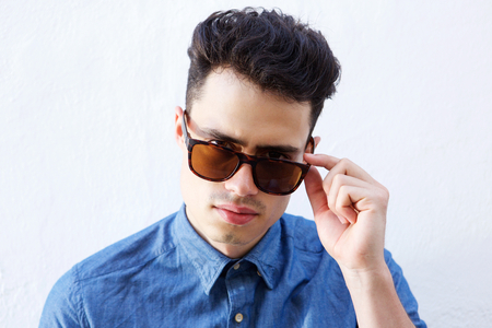 cool guy: Close up portrait of a cool young guy peeking over sunglasses Stock Photo