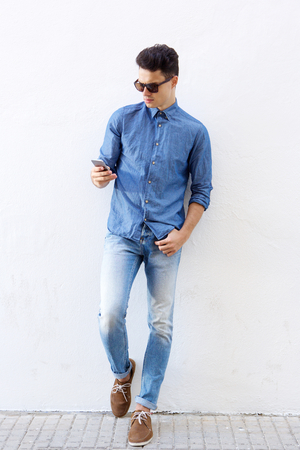 Full body cool hipster guy standing by white background reading mobile phone message Imagens - 44122821