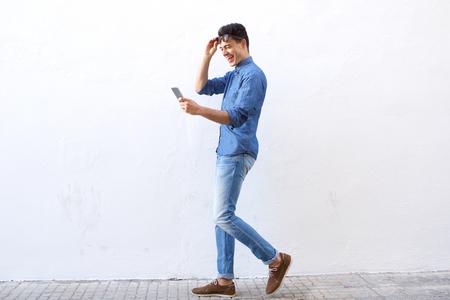 Full length kant portret van een gelukkige jonge man lopen op straat op zoek naar de mobiele telefoon