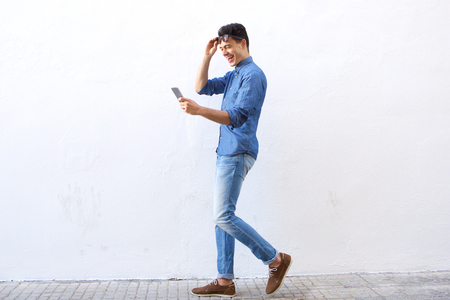 Full length side portrait of a happy young man walking on street looking at mobile phone