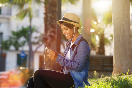 lady on phone: Portrait of a young african american woman listening to music on cell phone Stock Photo