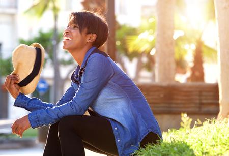 visage femme profil: portrait de côté d'une jeune femme noire souriante à l'extérieur dans le parc
