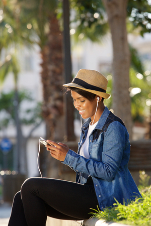 young black girl: Portrait of a cool young black woman listening to music with earphones