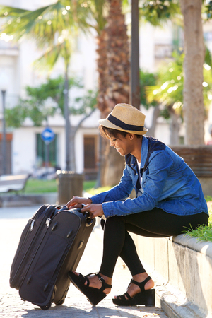 beautiful black woman: Portrait of a beautiful black woman sitting outside with suitcase