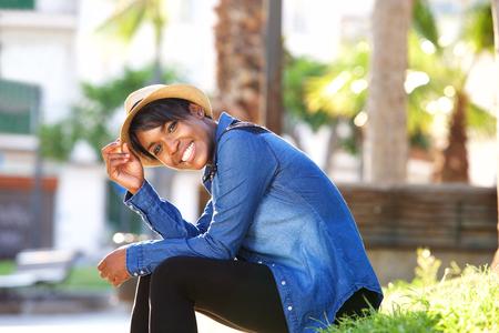 公園で座っている笑顔の若い黒人女性の側面の肖像画