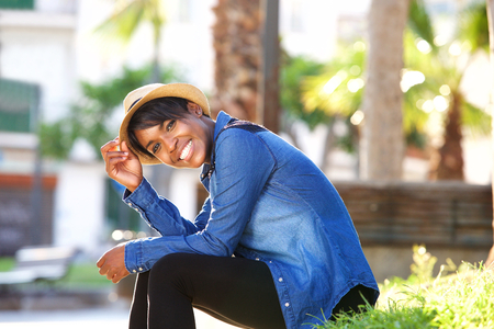 woman pose: Side portrait of a smiling young black woman sitting in park