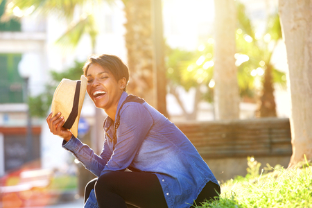 mannequin africain: Portrait de côté d'une jeune femme insouciante rire extérieur