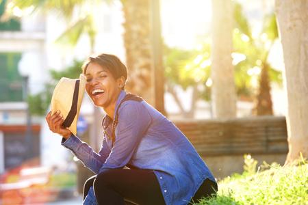 lachendes gesicht: Side Porträt einer unbeschwerte junge Frau draußen lachen Lizenzfreie Bilder
