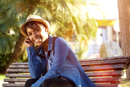 modelos negras: Retrato de una joven mujer afroamericana sonriente sentado fuera