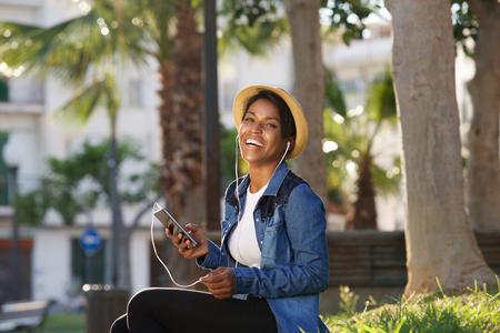 Retrato de uma jovem mulher negra rindo com telefone celular