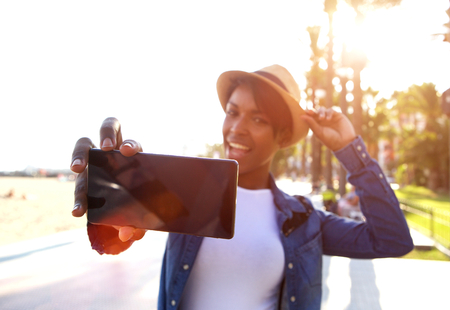 happy african: Close up portrait of a smiling black woman taking selfie while on vacation