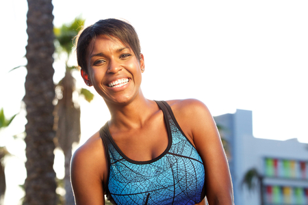 Close up portrait of an sporty attractive african american woman laughing