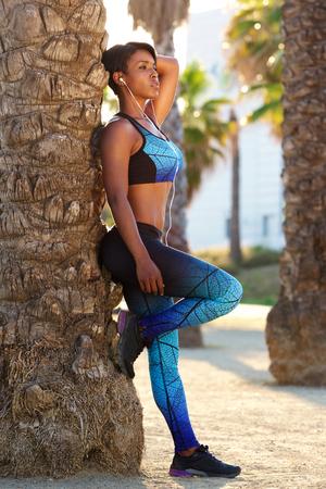 atletismo: Retrato de cuerpo entero de una atractiva mujer deportivo negro que se relaja afuera Foto de archivo