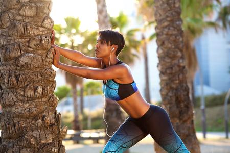 fitnes: Portret van een mooie zwarte vrouw die zich uitstrekt workout routine