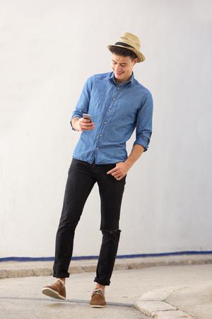 Ganzkörper-Porträt einer lächelnden jungen schönen Mann zu Fuß und auf der Suche Handy Standard-Bild