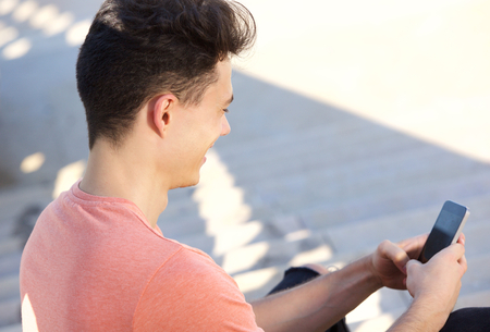 chat: Side portrait of a young guy typing text message on cell phone Stock Photo
