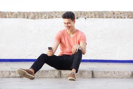 bonhomme blanc: Portrait d'un mec cool assis sur le trottoir en regardant téléphone mobile