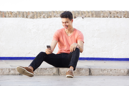 the guy: Portrait of a cool guy sitting on sidewalk looking at mobile phone Stock Photo