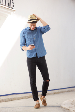 Full length portrait of a cheerful guy walking and reading text message on mobile phone