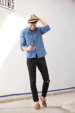 moda: Retrato de cuerpo entero de un hombre alegre caminar y leer mensajes de texto en el teléfono móvil