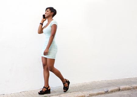falda corta: Retrato de la cara de cuerpo entero de una mujer joven y atractiva caminando por la calle con el teléfono celular