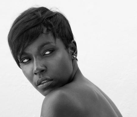 negras africanas: Close up blanco y negro retrato de un modelo de moda femenina posando sobre fondo blanco