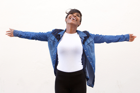 arms outstretched: Portrait of a carefree young woman standing with arms spread open Stock Photo