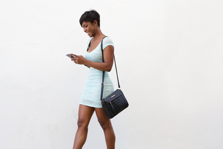 Side portrait of an attractive africana american woman walking and looking at cell phone Stock Photo