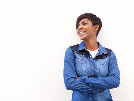 modelos negras: Retrato de una mujer joven alegre de pie con los brazos cruzados sobre fondo blanco