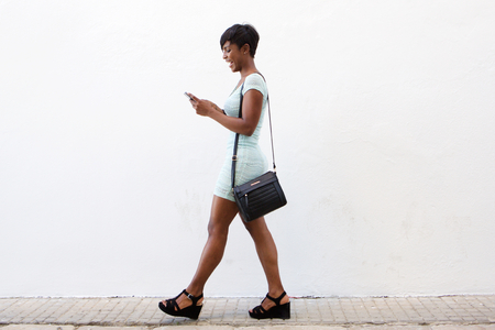 woman skirt: Full body side portrait of a smiling african american young woman walking and looking at cell phone