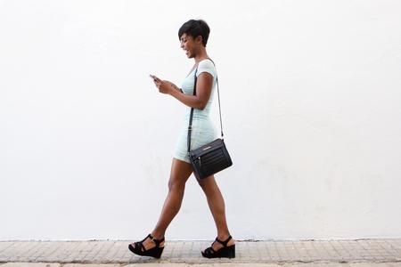 falda corta: Todo el cuerpo lateral retrato de una sonriente afroamericano joven mujer caminando y mirando al tel�fono celular
