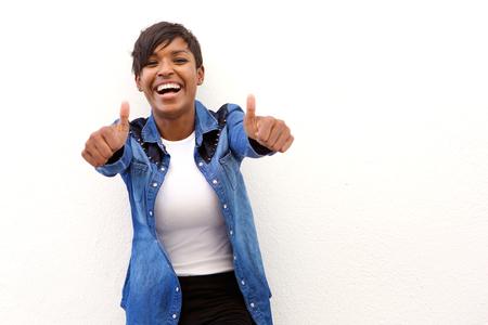 Portrét mladé ženy se smát s palci nahoru znamení