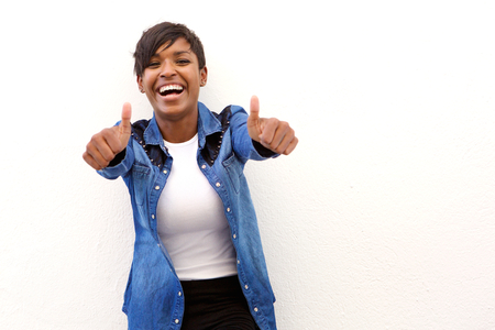 Portrait of a young woman laughing with thumbs up sign Imagens