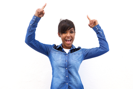 Portrait of a smiling black woman pointing fingers up to copy space on white background