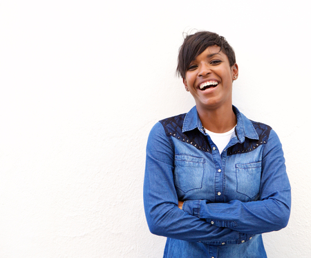 woman standing: Portrait of a young woman laughing with arms crossed against white background Stock Photo