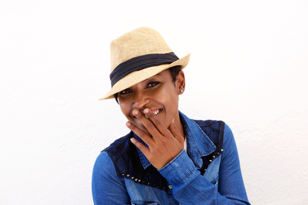 Close up portrait of a cute african american woman smiling with hand covering mouth photo