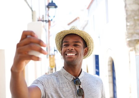 cell phone: Smiling young man taking selfie on vacation