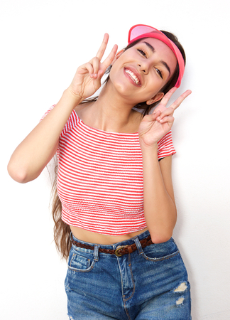 woman posing: Portrait of a cute girl with peace hand sign smiling against white background