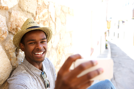 holding close: Cheerful young man taking selfie on vacation