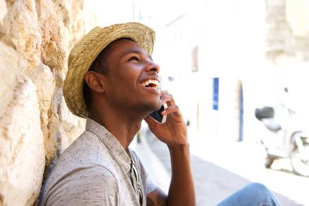 hablando por telefono: Hombre negro joven sonriente y hablando por teléfono móvil fuera