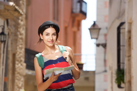 travel woman: Portrait of a young travel woman walking in town with bag and map Stock Photo