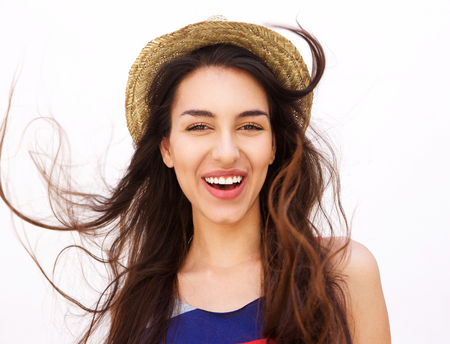 girl in a hat: Close up portrait of a smiling girl with long hair and hat posing against white background